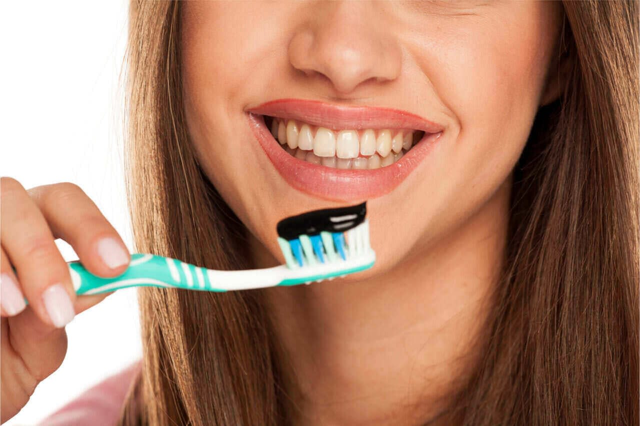 a girl using an activated charcoal toothpaste